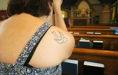 woman dove tat in pew - medium